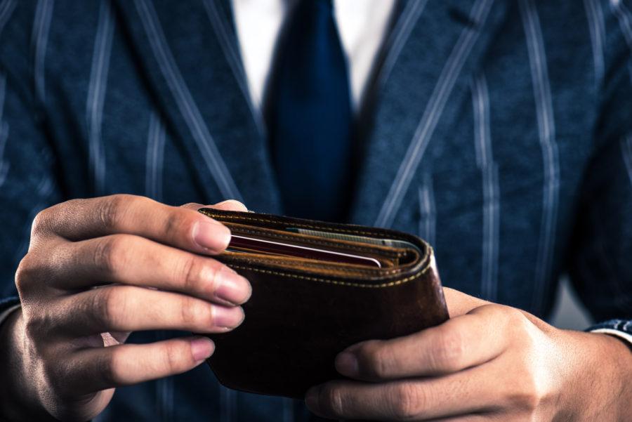 Mężczyzna z garniturem trzymający w dłoniach portfel